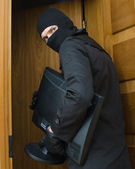Male burglar in mask breaking into the house and stealing monitor — Stock Photo