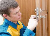 Young handyman in uniform changing door lock — Stock Photo
