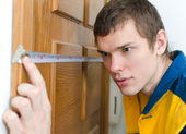 Young handyman in uniform working with measure tape — Stock Photo
