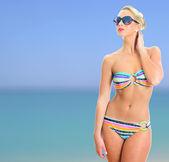 Blonde girl in striped bikini and sunglasses over sea background — Stock Photo
