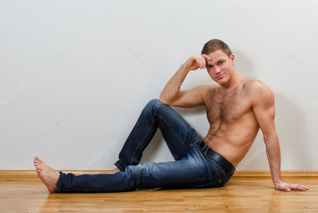 handsome guy in jeans with bare torso sitting on the floor near the wall stock photo. Black Bedroom Furniture Sets. Home Design Ideas