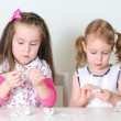 Two little girls sculpting using clay — Stock Photo #21558871