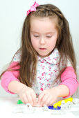 Cute undistracted girl sculpting using clay — Stock Photo