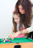 Mother teaching daughter play billiard — Stock Photo