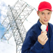Young electrician in uniform with bulb on transmission tower background — Stock Photo