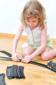 Pretty little girl playing with railway — Stock Photo