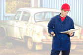 Young handyman reading manual over old car background — Stock Photo