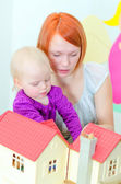 Child and their mother playing with dollhouse — Stock Photo
