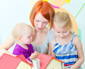 Children and their mother playing with dollhouse — Stock Photo
