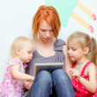 Mother and her daughters using tablet pc — Stock Photo