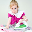 Cute little girl ironing clothes — Stock Photo