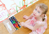 Pretty little girl painting sitting on the floor. Top view — Stok fotoğraf