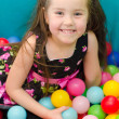 Happy little girl sitting in colourful balls — Stock Photo