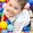 Happy little boy sitting in colourful balls — Stock Photo