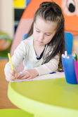 Little girl is drawing with pen in preschool — Stock Photo