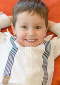 Smiling little boy lying with arms crossed — Stock Photo