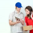Young courier deliver package to pretty woman — Stock Photo #24394071