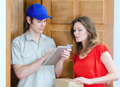 Young courier deliver package to pretty woman — Stock Photo