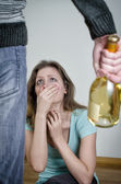 Home violence concept. Frightened woman and male hand holding bottle of wine — Stock Photo