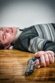 Man with gun laying on the floor — Stock Photo