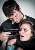 Man with gun threaten woman — Stock Photo