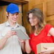 Stock Photo: Young courier deliver package to pretty woman