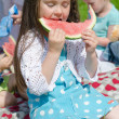 Pretty little girl eating watermelon in the park — Stock Photo #26886375
