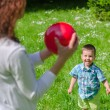 Mother and child playing with the ball outdoors — Stock Photo #26886615