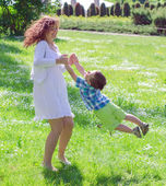 Mother and son spinning in summer park — Stock Photo