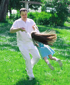 Father and daughter spinning in summer park — Stock Photo