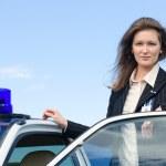 Young female FBI agent standing near car open door — Stock Photo #27344653