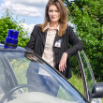Young female FBI agent standing near car open door — Stock Photo