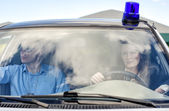 Two young detectives driving to crime scene. Windscreen view — Stock Photo