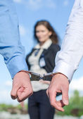 Close up view of hands in handcuffs and female FBI agent on background — Stock Photo