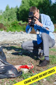 Young criminalist takes picture of crime scene — Stock Photo