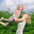Mother and daughter spinning in summer park — Stock Photo