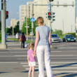 Foto Stock: Mother and child crossing road. Back view.