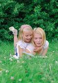 Mor och dotter läsa bok i parken — Stockfoto