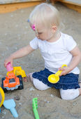 Toddler plays with toys on sandbox — Stock Photo