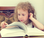 Cute little girl reading a book — Stock Photo