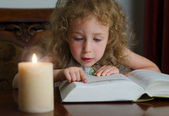 Cute little girl sitting in the dark with burning candle and reading a book — Zdjęcie stockowe