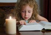 ろうそくを燃やす本を読むのと暗闇の中で座っているかわいい女の子 — ストック写真