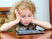 Cute little girl using tablet pc — Zdjęcie stockowe