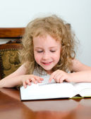 Cute little smiling girl reading a book — Stock Photo
