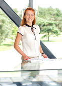 Young pretty woman in modern glass interior with a book — Stock Photo