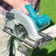 Handyman using saw mashine outdoors — Stock Photo