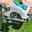 Handyman using hand-held saw machine outdoors — Stock Photo