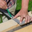 Male hands measuring and marking wooden plank outdoors — Foto Stock