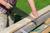 Handyman sawing long wooden plank outdoors — Stock Photo