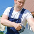 Handsome handyman sawing long wooden plank outdoors — Stock Photo